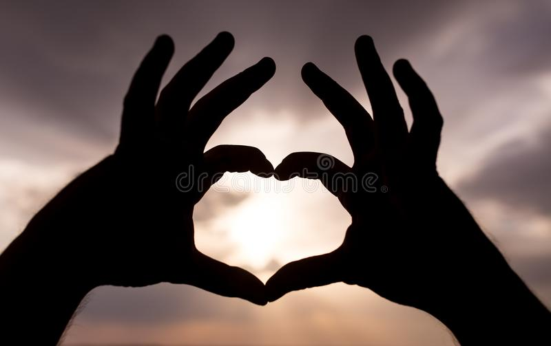 Silhouette of hands in form of heart on the background of sunset stock photography