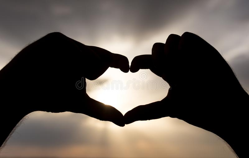 Silhouette of hands in form of heart on the background of sunset stock photos