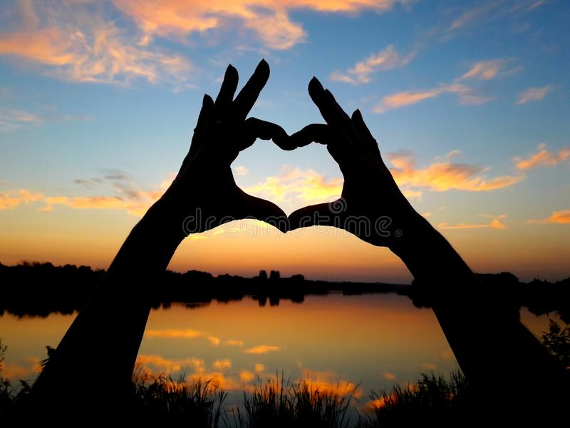 Silhouette of hands in the shape of a heart against the backdrop of a beautiful sunset. stock images
