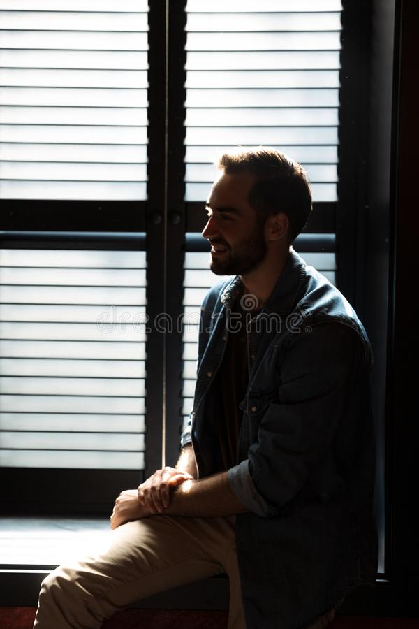 Silhouette of handsome joyful man standing in dark room at shadow blinds. Silhouette of handsome joyful man standing in dark room against the sunlight from royalty free stock image