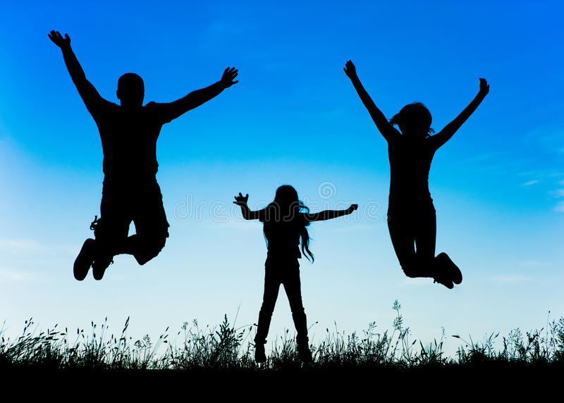 Silhouette of a happy active family jumping stock photo