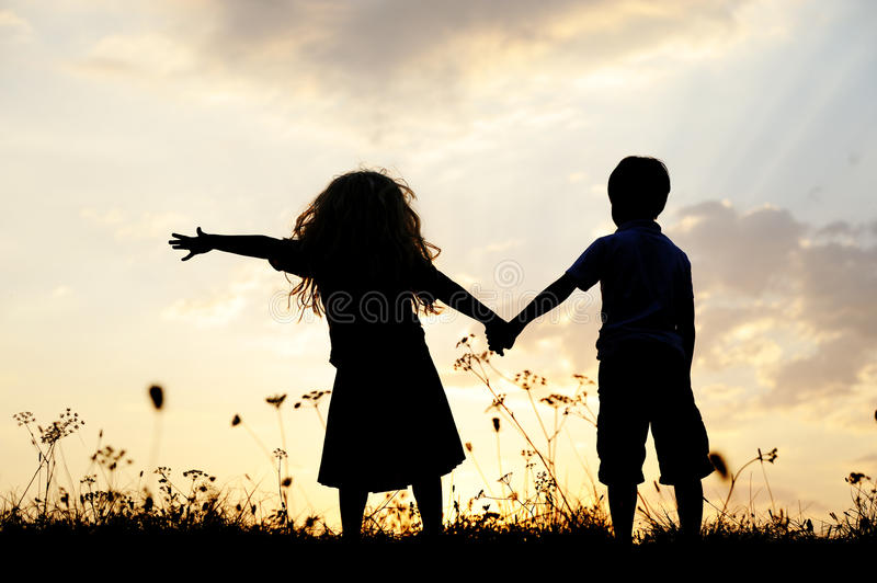 Silhouette, happy children playing on meadow. Silhouette, two happy children playing on meadow, sunset, summertime stock photography