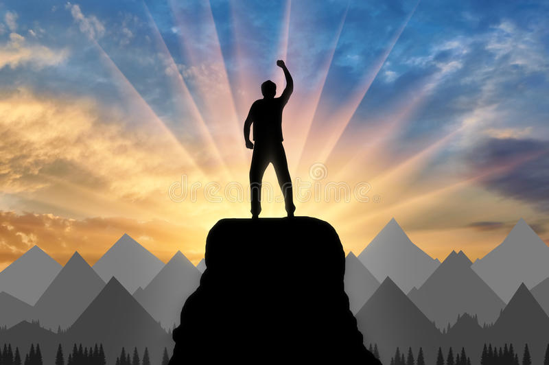 Silhouette happy climber on a mountain top stock images