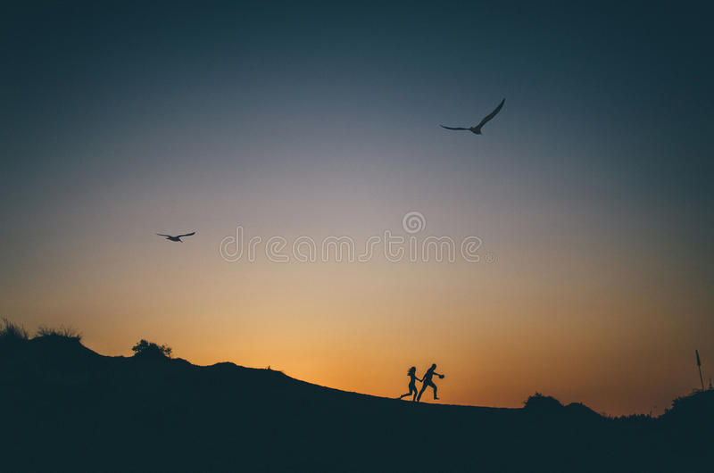 Silhouette of happy couple running at sunset stock images