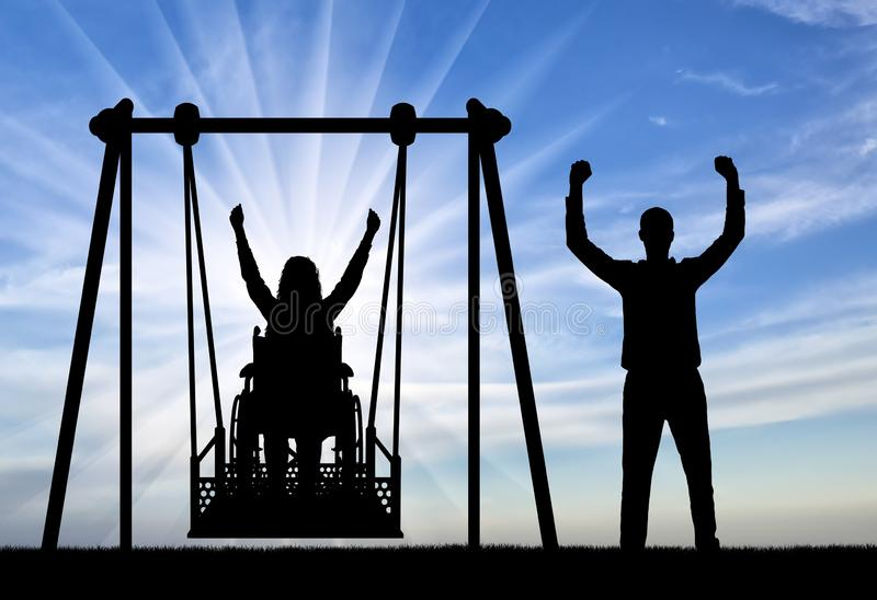 Silhouette of a happy couple, a woman wheelchair user on an adaptive swing and a healthy man nearby. Concept of the lifestyle of people with disabilities stock photos