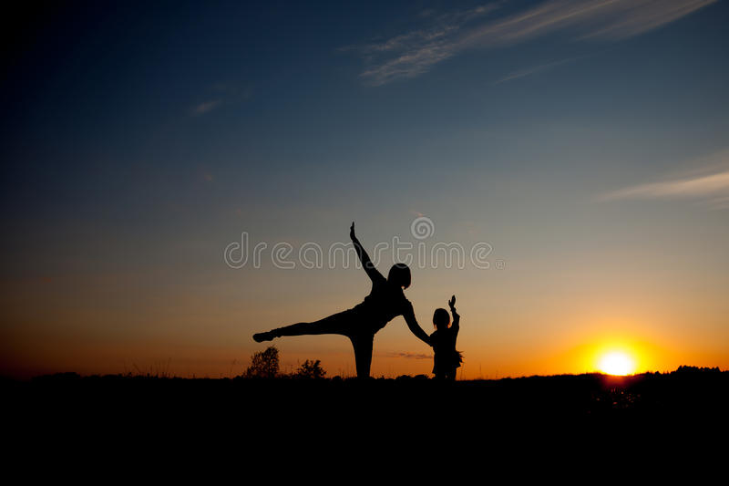 Silhouette, happy daugther with mother at sunset, summertime stock photo