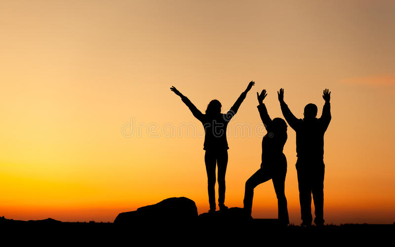 Silhouette of a happy family with arms raised up against beautiful sky. Summer Sunset. Landscape stock image