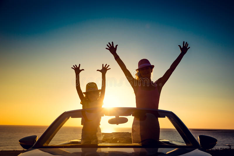 Silhouette of happy family at the beach. Against sunset sky and sea background. People traveling by car. Summer vacation and travel concept royalty free stock photo