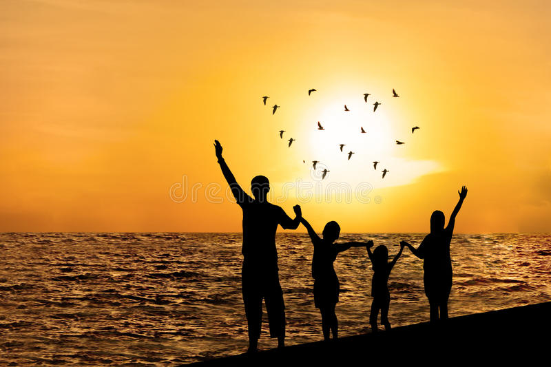 Silhouette of happy family on beach. Watching sunset together stock images