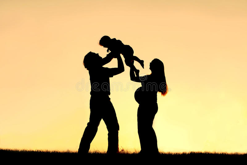 Silhouette of Happy Family Celebrating Pregnancy. A silhouette of a happy family of three people, father, child and pregnant mother, are celebrating and praising royalty free stock photography