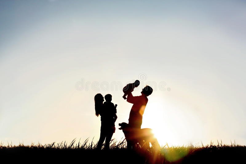 Silhouette of Happy Family and Dog. A silhouette of a happy family of four people, mother, father, baby, and child, and their dog in front of a sunsetting sky stock photography