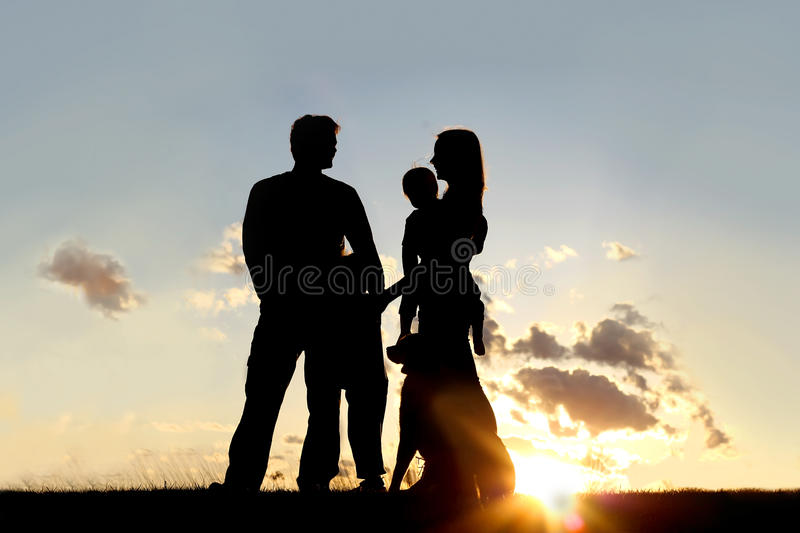 Silhouette of Happy Family and Dog Outside at Sunset. A silhouette of a happy family of four people, mother, father, child and baby, are standing outside at royalty free stock photography