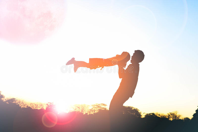 Silhouette of happy family father and child playing outdoors. At sunset stock image