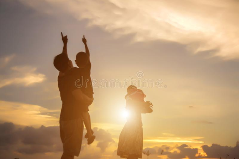 silhouette of happy family father mother and son playing outdoors a royalty free stock photos