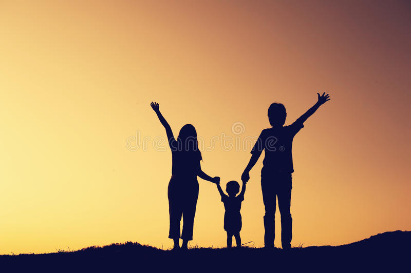 Silhouette of happy family father mother and son playing at suns stock images