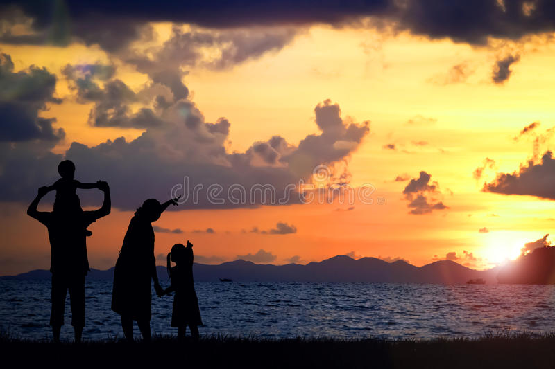 A silhouette of a happy family, mother, father,girl,son and infant (women pregnancy) on sunsetbach (copy space or text on right. Area royalty free stock image