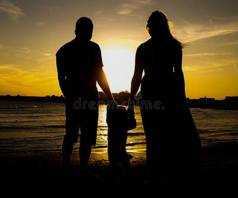 Happy family standing on beach against sky during sunset. Father, mother and daughter who are holding their hands royalty free stock photography