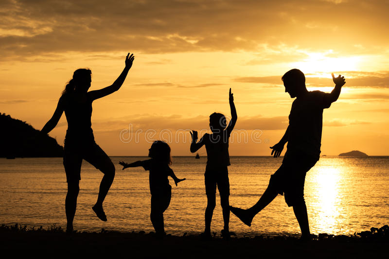 Silhouette of happy family who playing on the beach at the sunset time. Silhouette of happy family who dancing on the beach at the sunset time. Concept of royalty free stock photography