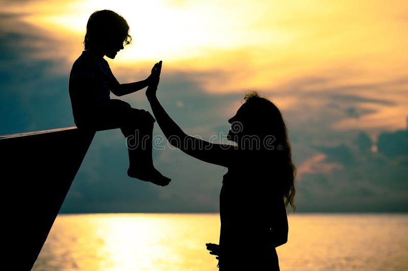 Silhouette of happy family who playing on the beach at the sunset time. Concept of friendly family royalty free stock photo