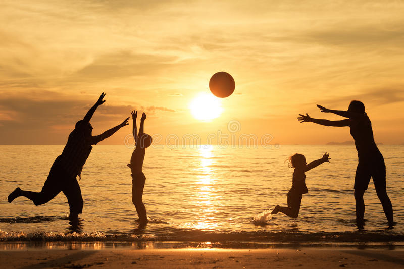 Silhouette of happy family who playing on the beach at the sunse. T time. Concept of friendly family stock photo