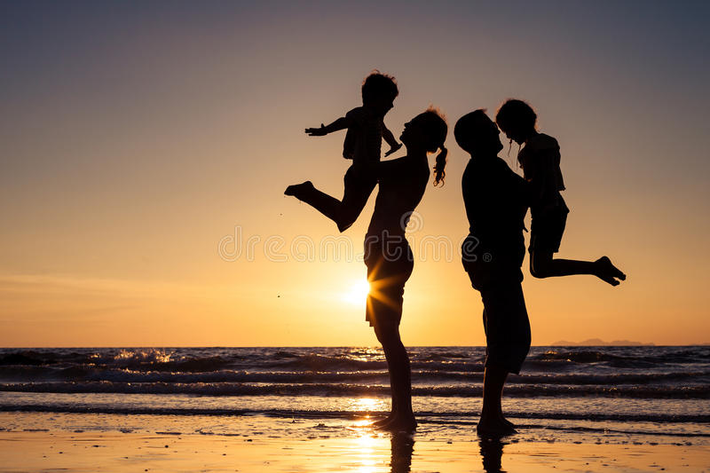 Silhouette of happy family who playing on the beach at the sunset time. stock photo