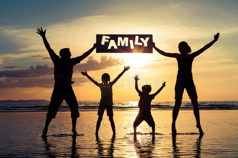 Silhouette of happy family who standing on the beach at the suns. Et time. People having fun on the sea. Concept of friendship forever and of summer vacation royalty free stock image
