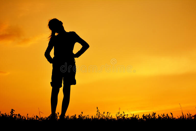 Silhouette of happy girl standing on grass field stock image