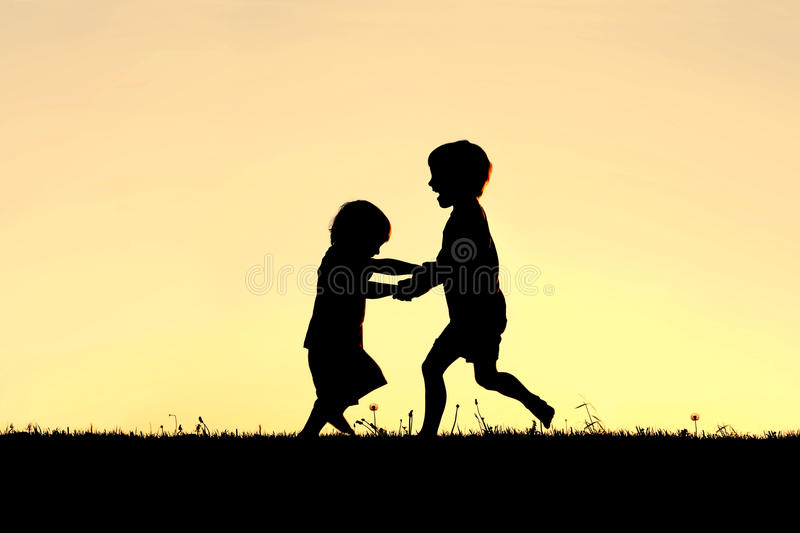 Silhouette of Happy Little Children Dancing at Sunset stock image