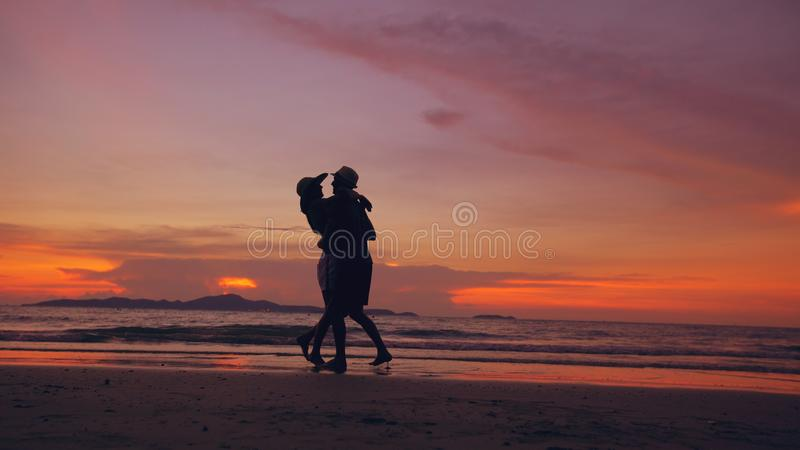 Silhouette of happy loving couple meet and play at the beach on sunset in ocean shore royalty free stock photo