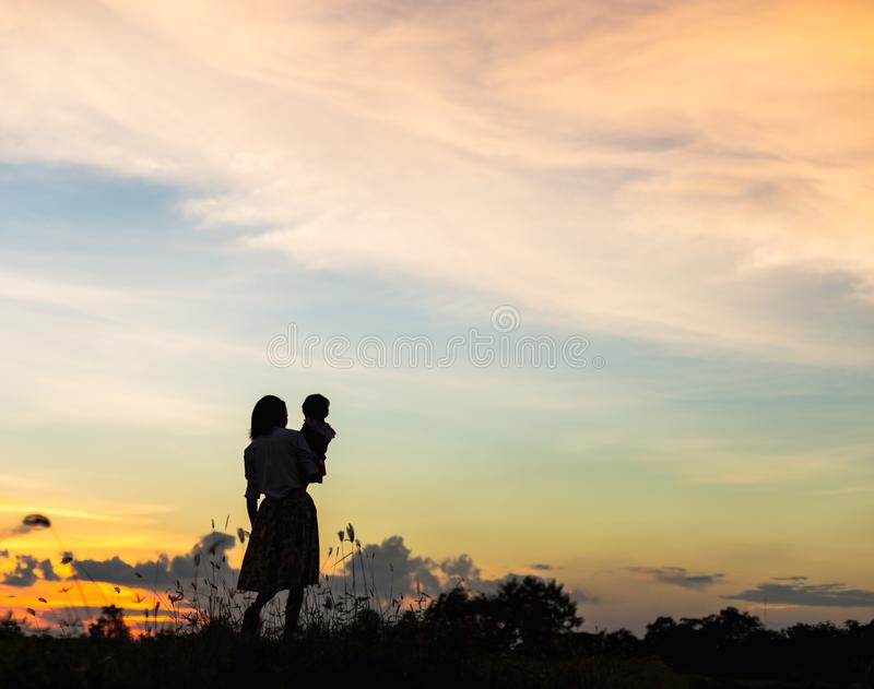 Silhouette Happy mother and daughter laughing together outdoors royalty free stock photo