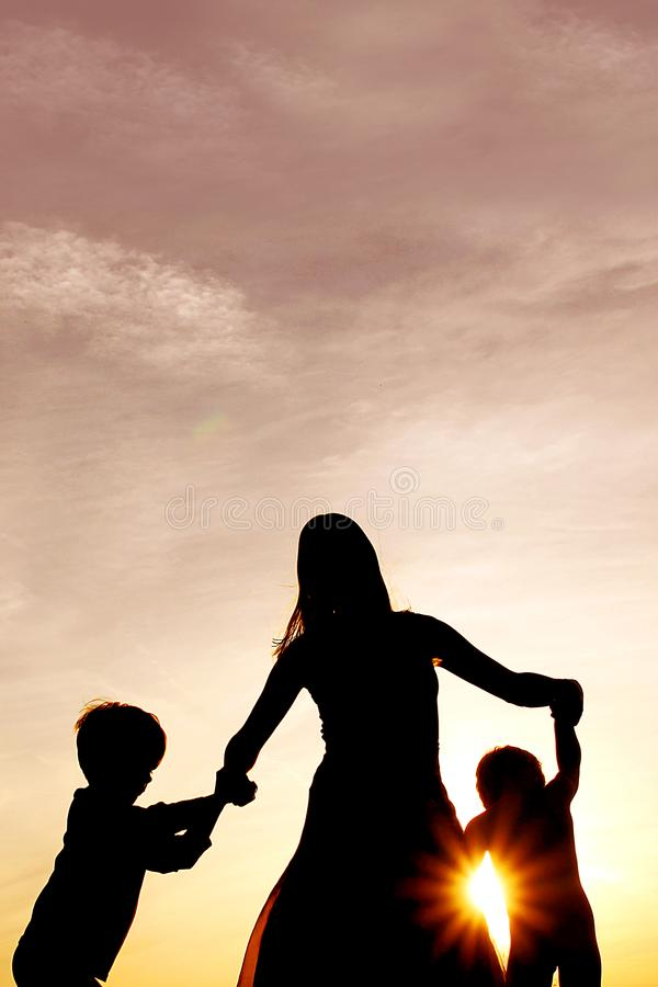 Silhouette of happy mother and little children dancing outside a royalty free stock images