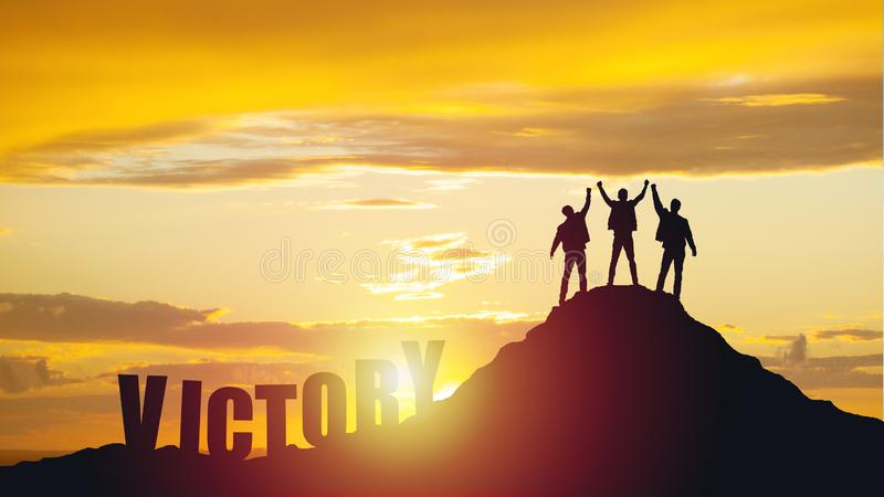 Silhouette of happy teamwork hold hands up as a business successful, business victory. stock photography