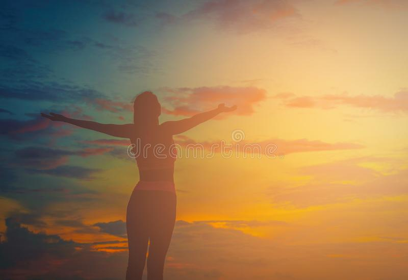 Silhouette happy woman on the beach at sunset. royalty free stock images