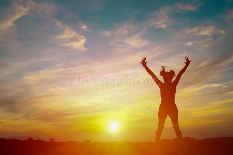Silhouette of a happy woman and sunset success story. Silhouette of a happy woman and sunset stock image