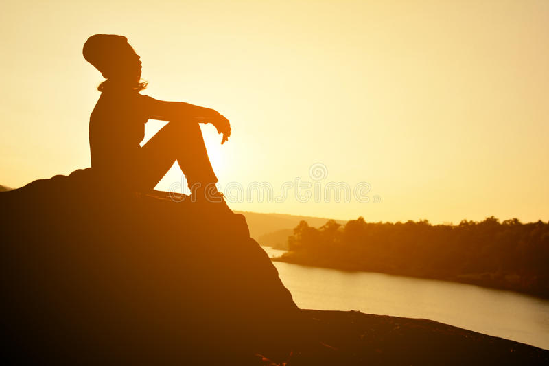 Silhouette of happy women on the rock near the river royalty free stock photos