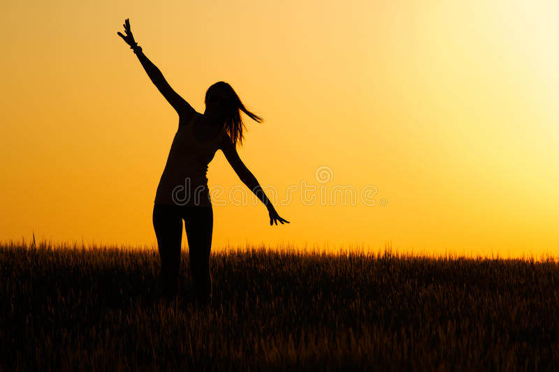 Silhouette of happy young girl in field. royalty free stock photos