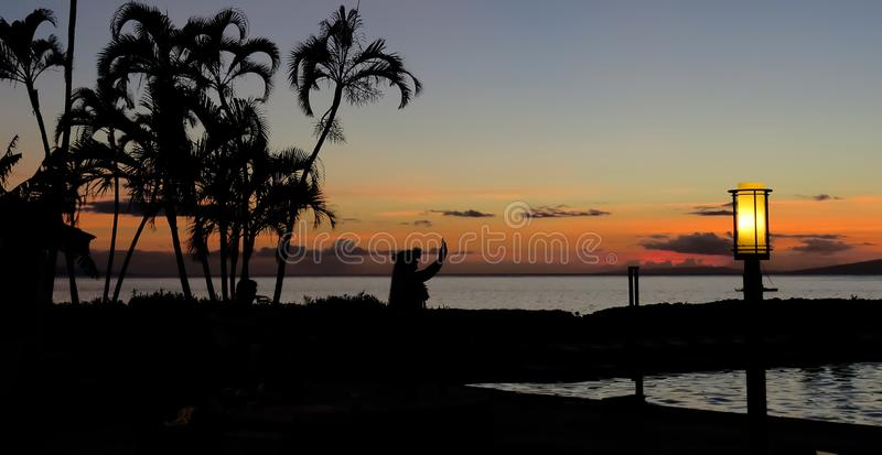 Silhouette of a Hawaiian hula dancer at sunset with palm trees on the beach, Lahaina, Maui, Hawaii. Silhouette of a Hawaiian hula dancer performing near the royalty free stock photography