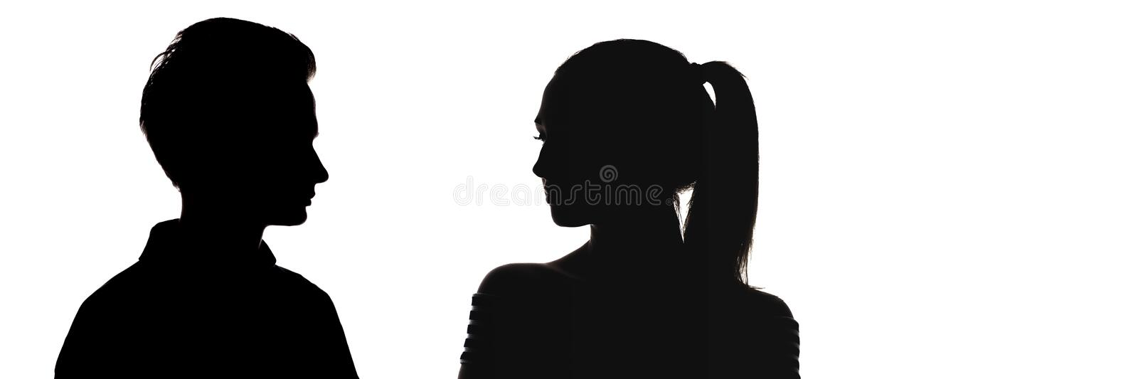 Silhouette head profile of guy and a girl looking at each other, faces of serious teenagers, comparison of genders, stock image