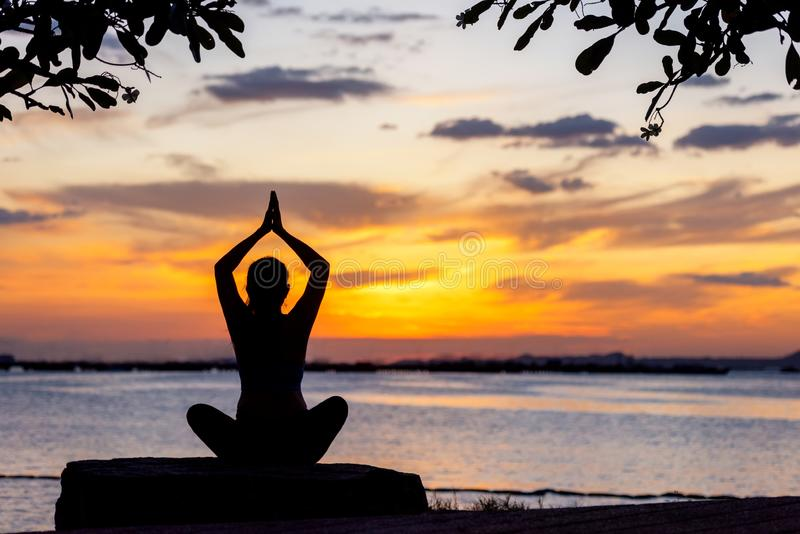 Silhouette healthy woman yoga balance body exercising vital meditate and practicing on the rock outdoor in the beach at sunset. stock photography