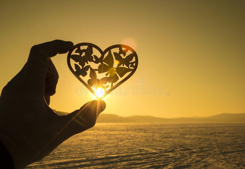 Silhouette of a heart and butterflies in the hands of a man against a background of sun rays. The idea: a day of lovers, Valentine`s Day, love stock photo