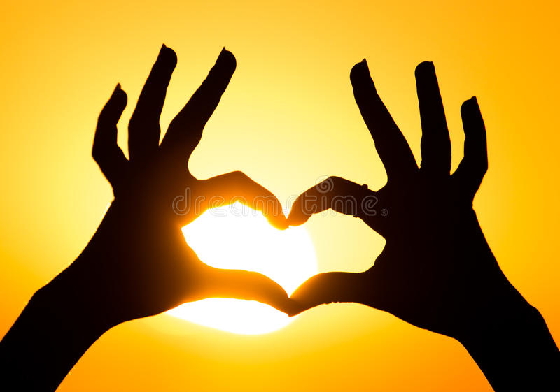 Silhouette of the heart by hands at sunset stock photo