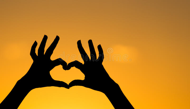 Silhouette of the heart by hands at sunset royalty free stock photography