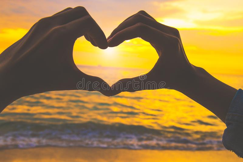 Silhouette heart shape with hand at the beach at sunset. royalty free stock photos