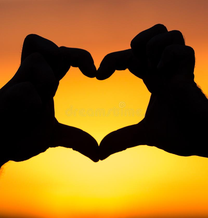 Silhouette of heart at sunset royalty free stock image