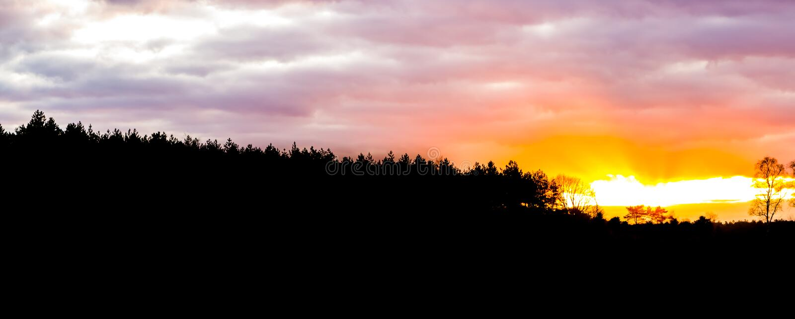 Silhouette of a heather landscape in the forest at sunset, sundown giving a colorful glow in the sky and clouds royalty free stock photos