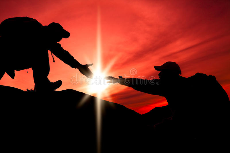 Silhouette of helping hand. Between two climber stock images