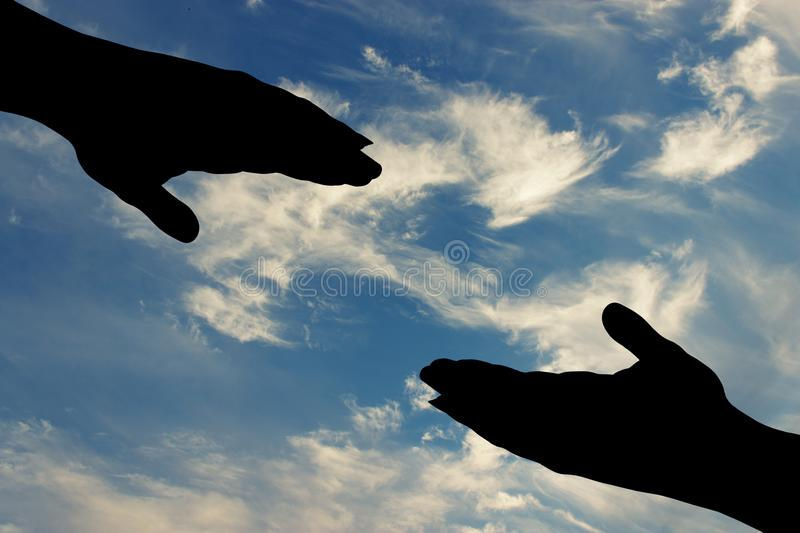 Silhouette of helping hand . Silhouette of helping hand on sky background royalty free stock photo