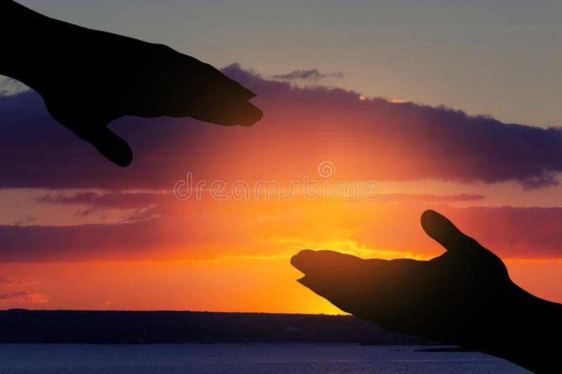 Silhouette of helping hand . Silhouette of helping hand on sky background stock images