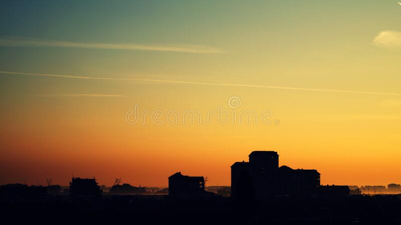 Silhouette of High Rise Building Under Golden Sun royalty free stock image