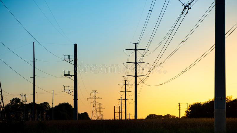 Silhouette High voltage electric tower on sunset time and sky on sunset background stock photography